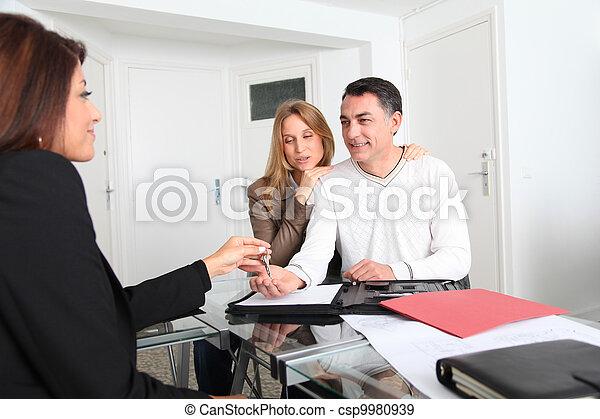 Una pareja firmando un contrato con un agente inmobiliario - csp9980939