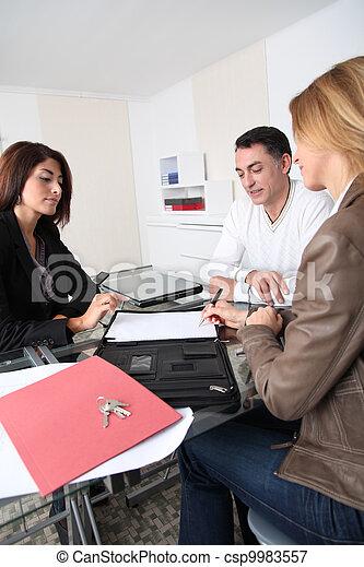Una pareja firmando un contrato con un agente inmobiliario - csp9983557