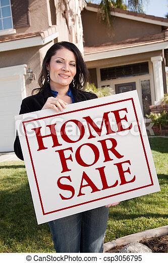 Una mujer que se queda en casa para vender bienes raíces frente a la casa - csp3056795