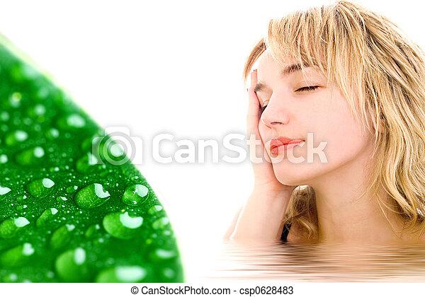 Mujer relajada y hoja verde con gotas de agua - csp0628483