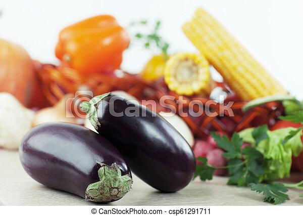 Berenjena en un fondo de vegetales frescos - csp61291711