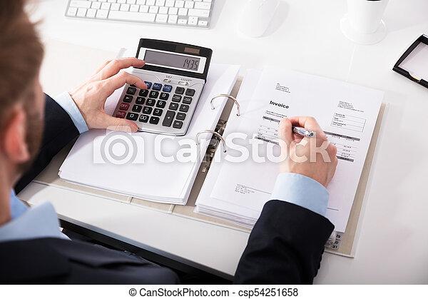 Hombre de negocios comprobando factura con calculadora - csp54251658