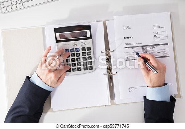 Hombre de negocios comprobando factura con calculadora - csp53771745