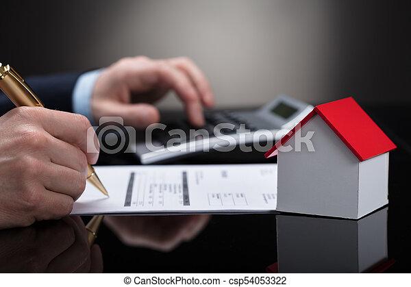 Hombre de negocios comprobando factura con calculadora - csp54053322