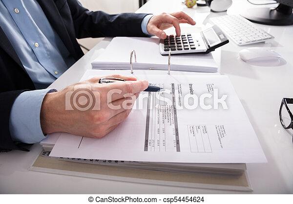 Hombre de negocios comprobando factura con calculadora - csp54454624