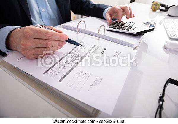 Hombre de negocios comprobando factura con calculadora - csp54251680
