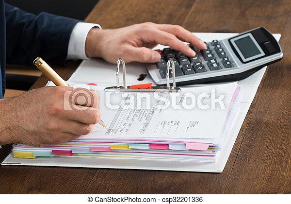 Hombre de negocios usando calculadora mientras comprobaba la factura en el escritorio - csp32201336
