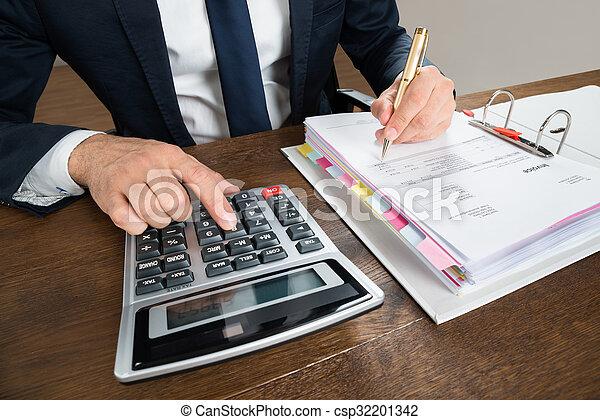 Hombre de negocios usando calculadora mientras comprobaba la factura en el escritorio - csp32201342