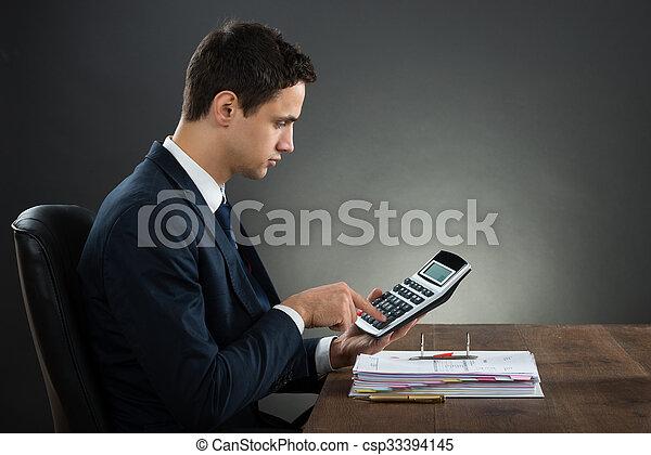 Hombre de negocios usando calculadora mientras comprobaba la factura en el escritorio - csp33394145