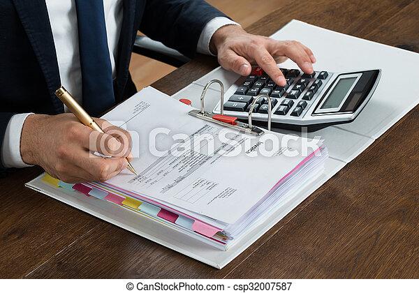 Hombre de negocios usando calculadora mientras comprobaba la factura en el escritorio - csp32007587