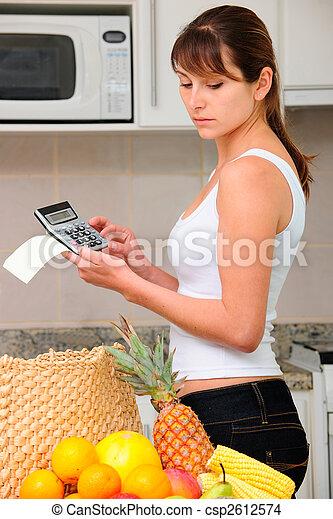 Una mujer comprobando cuentas con calculadora en la cocina - csp2612574