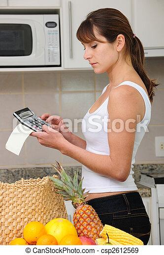 Una mujer comprobando cuentas con calculadora en la cocina - csp2612569