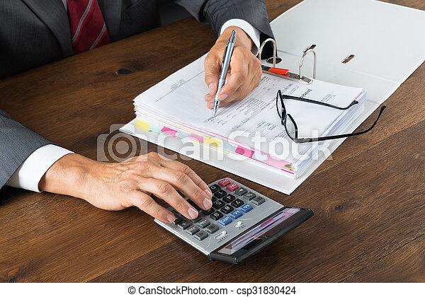 Contable comprobando factura con calculadora - csp31830424