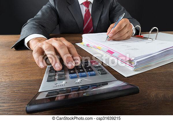 Contable comprobando factura con calculadora - csp31639215