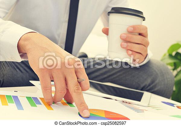 Un joven hombre de negocios revisando unas gráficas - csp25082597