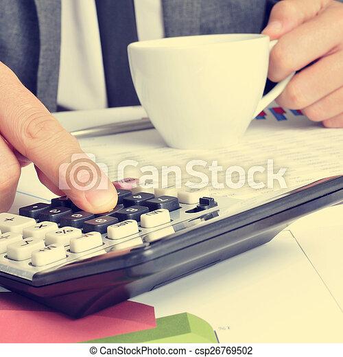 Un joven hombre de negocios revisando cuentas - csp26769502