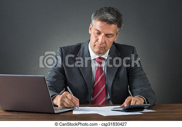 Hombre de negocios revisando facturas en el escritorio - csp31830427