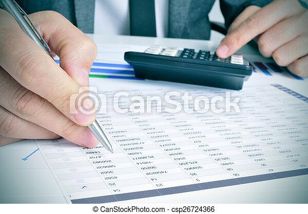 Un joven hombre de negocios revisando cuentas - csp26724366