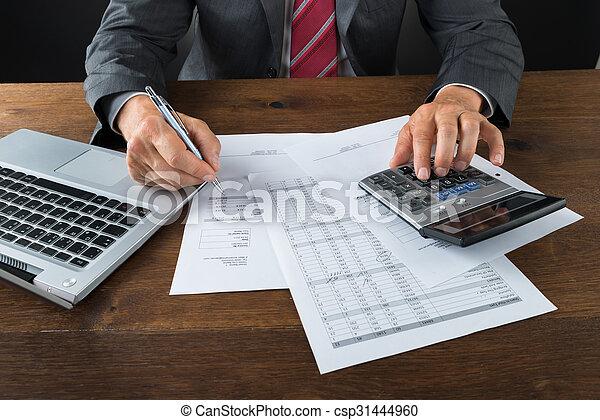 La mitad de un hombre de negocios revisando facturas en el escritorio - csp31444960
