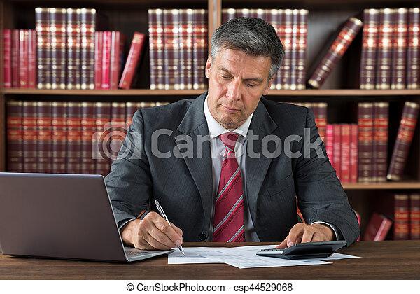 Hombre de negocios revisando facturas en el escritorio - csp44529068