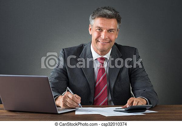 Hombre de negocios revisando facturas en el escritorio - csp32010374