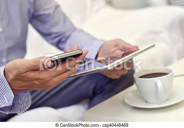 Hombre de negocios revisando su smartphone y su tablet - csp40448469