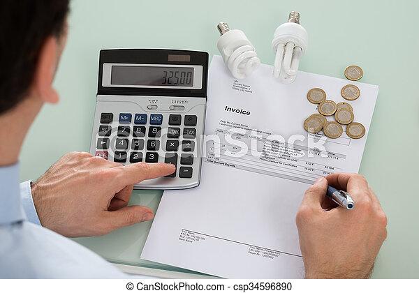 Hombre de negocios comprobando factura con calculadora - csp34596890