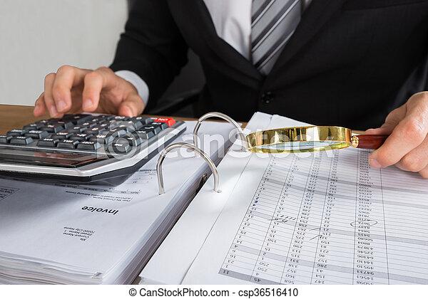 Un joven hombre de negocios comprobando la factura - csp36516410
