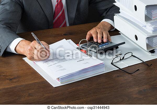 Hombre de negocios revisando recibos en el escritorio - csp31444943