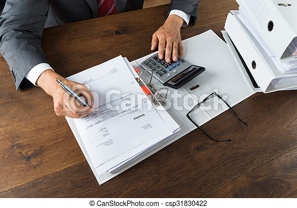Hombre de negocios revisando recibos en el escritorio - csp31830422