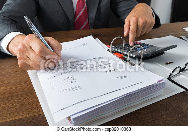 Hombre de negocios revisando recibos en el escritorio - csp32010363