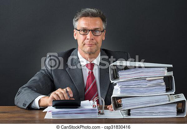 Hombre de negocios comprobando factura con calculadora en el escritorio - csp31830416