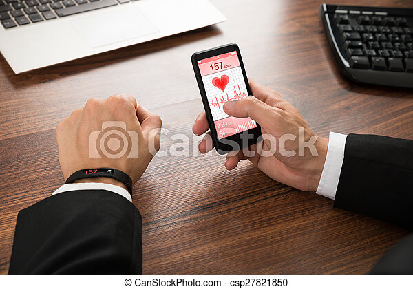 Hombre de negocios comprobando la frecuencia cardíaca - csp27821850