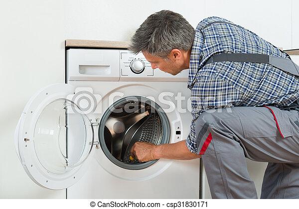 Reparador revisando la lavadora en casa - csp31830171