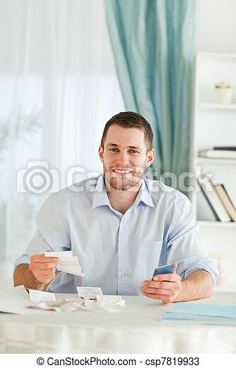 Hombre de negocios con calculadora de manos comprobando facturas - csp7819933