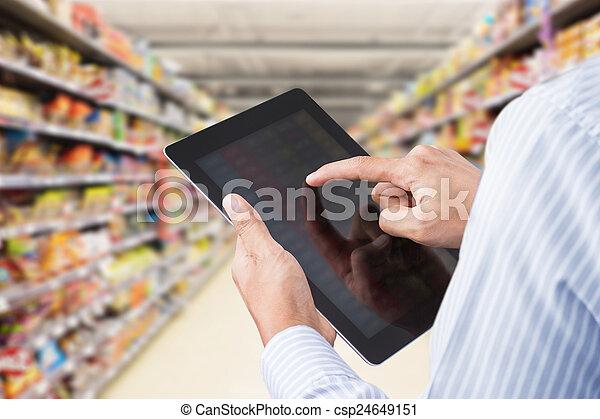 Revisando el inventario en el supermercado - csp24649151