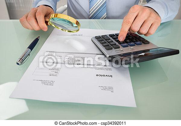 Hombre de negocios comprobando factura con lupa - csp34392011