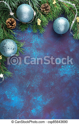 Vertical Christmas frame made of pine branches with yellow dried flowers and blue toys on a blue concrete background. - csp85643690