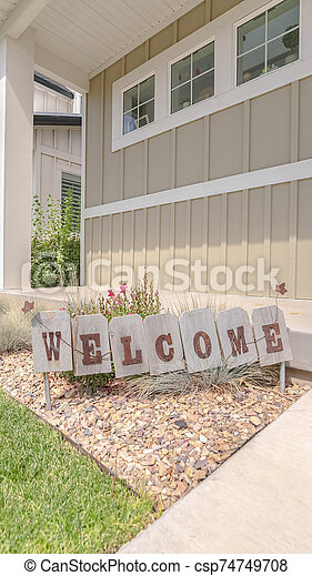 Vertical frame Welcome sign in front garden of traditional home - csp74749708