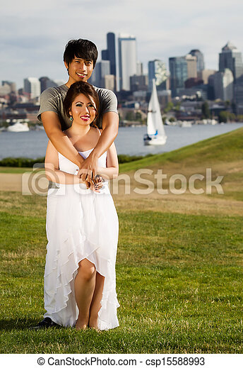 Vertical photo of young adult couple, facing forward, holding each with city of Seattle and harbor in Background - csp15588993