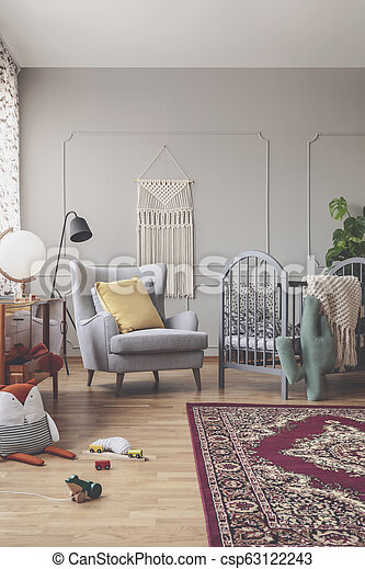 Vertical view of mid century baby room with rustic rug, comfortable grey armchair and wooden crib with patterned bedding - csp63122243