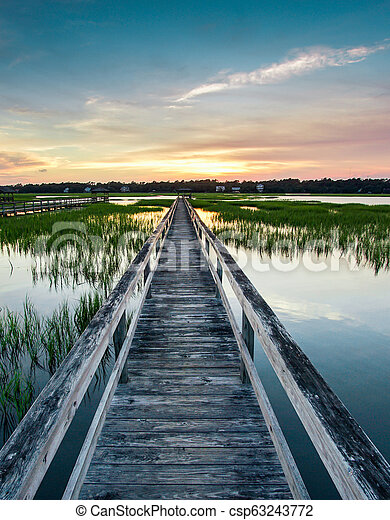 vertical view of sunset over coastal waters with a very long wooden boardwalk - csp63243772