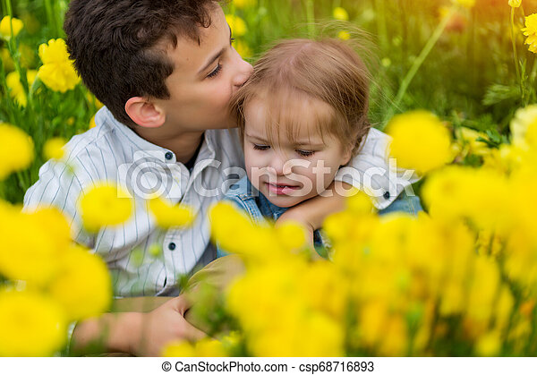 Very cute beautiful little sister hugging her big brother. S sweet - csp68716893