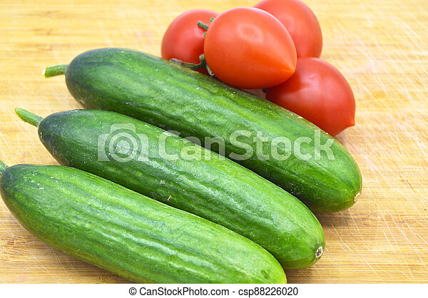 Very fresh green cucumbers and tomato on cutting board - csp88226020