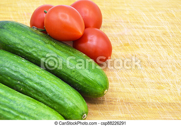 Very fresh green cucumbers and tomato on cutting board - csp88226291