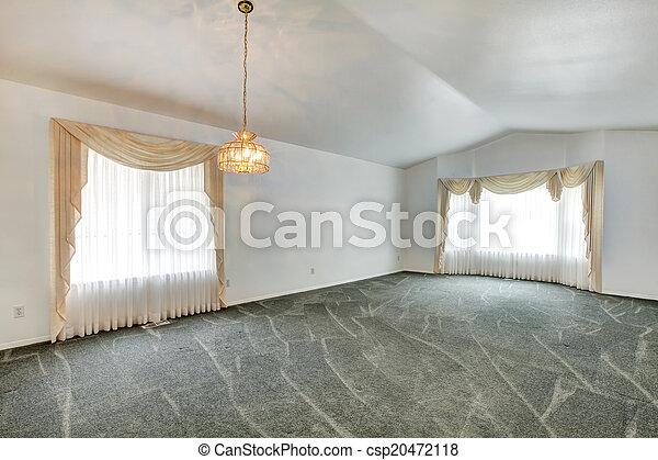 Un salón vacío con techo acorazado y piso de alfombra verde - csp20472118