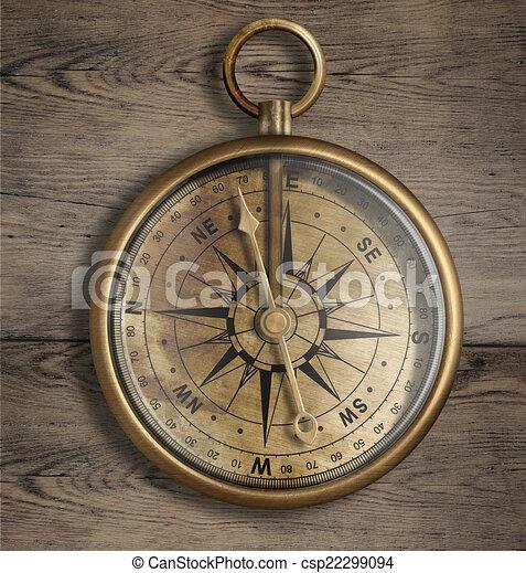 La vieja brújula de bronce en la mesa de madera se cierra - csp22299094
