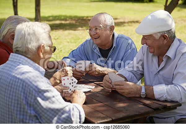 Egresados activos, un grupo de viejos amigos jugando a las cartas en el parque - csp12685060