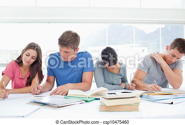 Vier Schüler sitzen nebeneinander und lernen - csp10475460