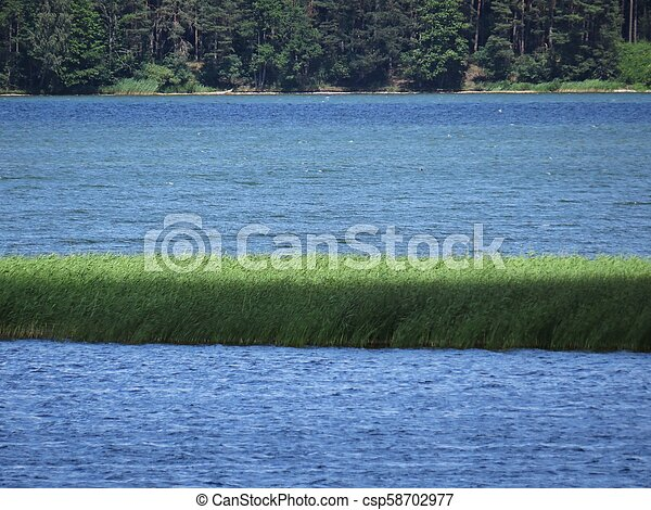 View at Panorama of Tranquil Lake with Trees and Clouds - csp58702977